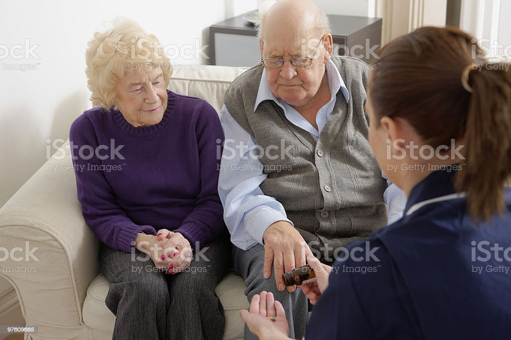 Nurse giving medicine to older couple at home royalty-free stock photo