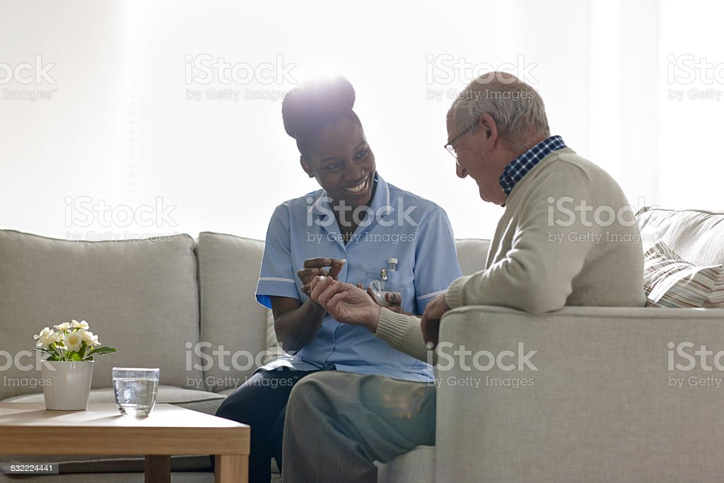 Nurse giving medicine to senior patient at home stock photo