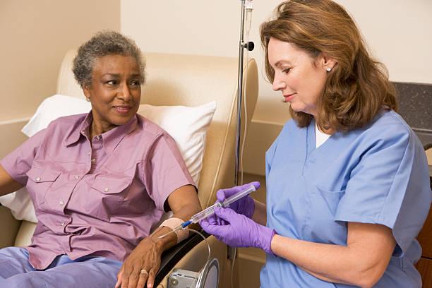 krankenschwester, die patienten injektion - chemotherapie stock-fotos und bilder