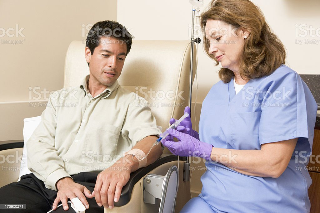 Nurse Giving Patient Injection Through Tube stock photo