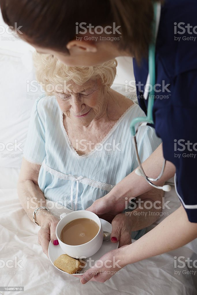 nurse giving senior woman a cup of tea in bed royalty-free stock photo