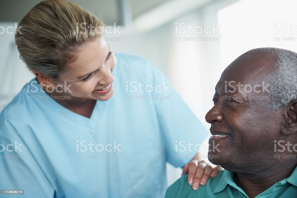 Nurse greeting a patient by putting her hand on his shoulder stock photo