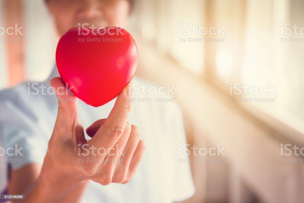 Manos de la enfermera sosteniendo corazón rojo en hospital.healthy y medichine el concepto y enfoque selectivo - foto de stock