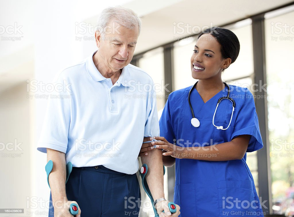 Nurse helping a senior patient in crutches royalty-free stock photo