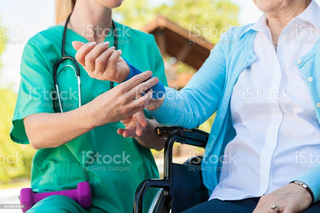 Nurse helping an injured senior woman in a wheelchair stock photo