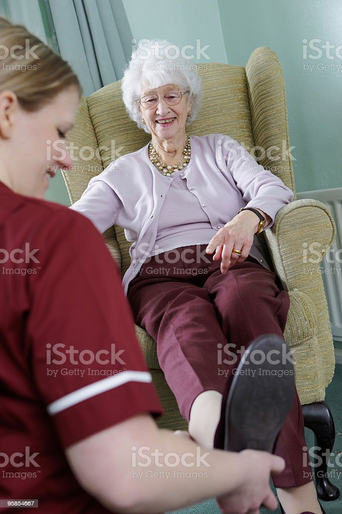 Nurse helping elderly lady to dress in a care home stock photo