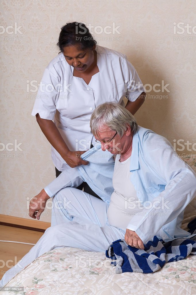Nurse helping elderly man getting dressed stock photo