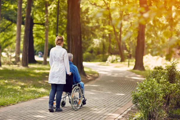 krankenschwester hilft älteren mann im rollstuhl im freien - hospiz stock-fotos und bilder