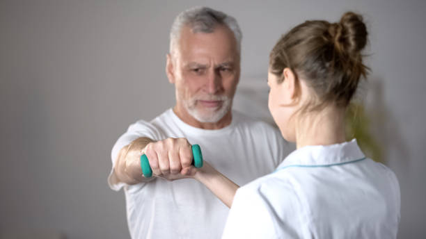 Nurse helping old man to lift dumbbell, cardiac rehabilitation, injury recovery Nurse helping old man to lift dumbbell, cardiac rehabilitation, injury recovery drug rehab stock pictures, royalty-free photos & images