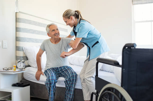 Nurse helping old patient get up stock photo