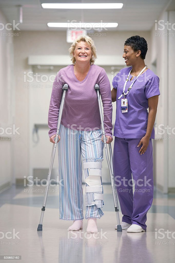 Nurse helping patient with crutches stock photo
