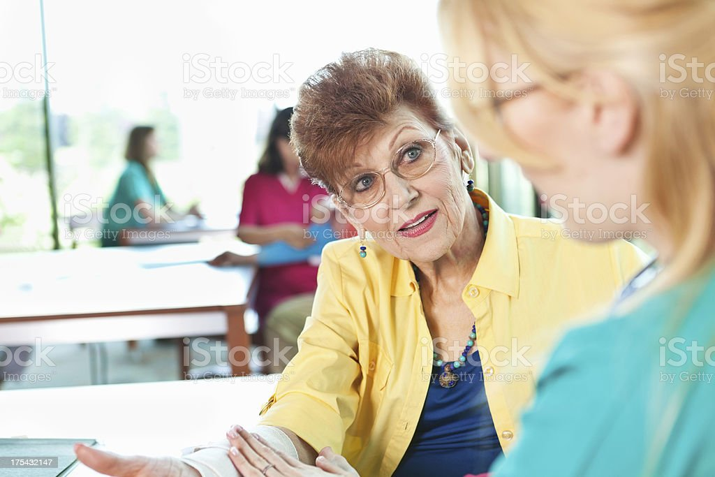 Nurse helping senior adult patient with injured arm royalty-free stock photo