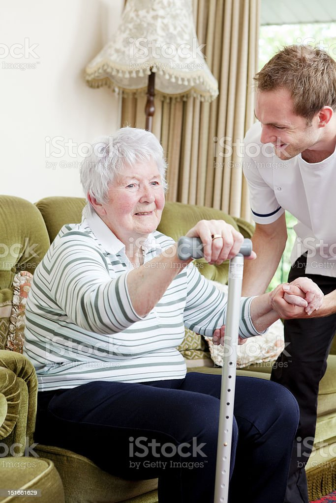 Nurse helping senior lady to her feet in care home stock photo