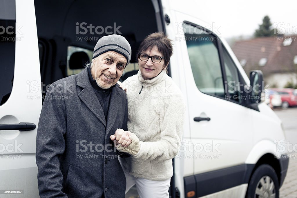 nurse helping senior man enter a van stock photo