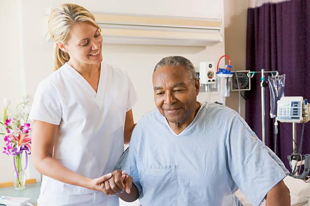 nurse helping senior man to walk - female nurse stock photos and pictures