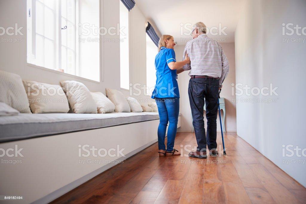Enfermeira, ajudando o homem sênior andar usando uma bengala - foto de acervo