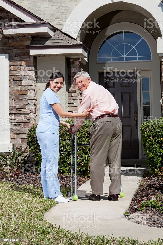 Nurse helping senior man with walker in front of house royalty-free stock photo