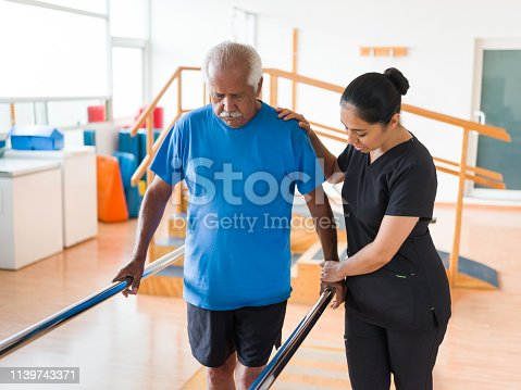 A female nurse helping a senior man to walk in the parallel bars.