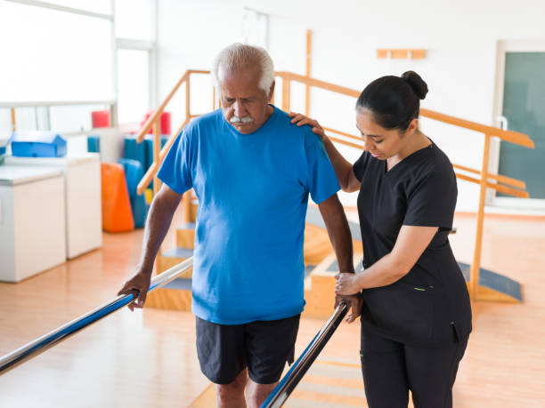 Nurse helping senior student walk in parallel bars A female nurse helping a senior man to walk in the parallel bars. recovery stock pictures, royalty-free photos & images