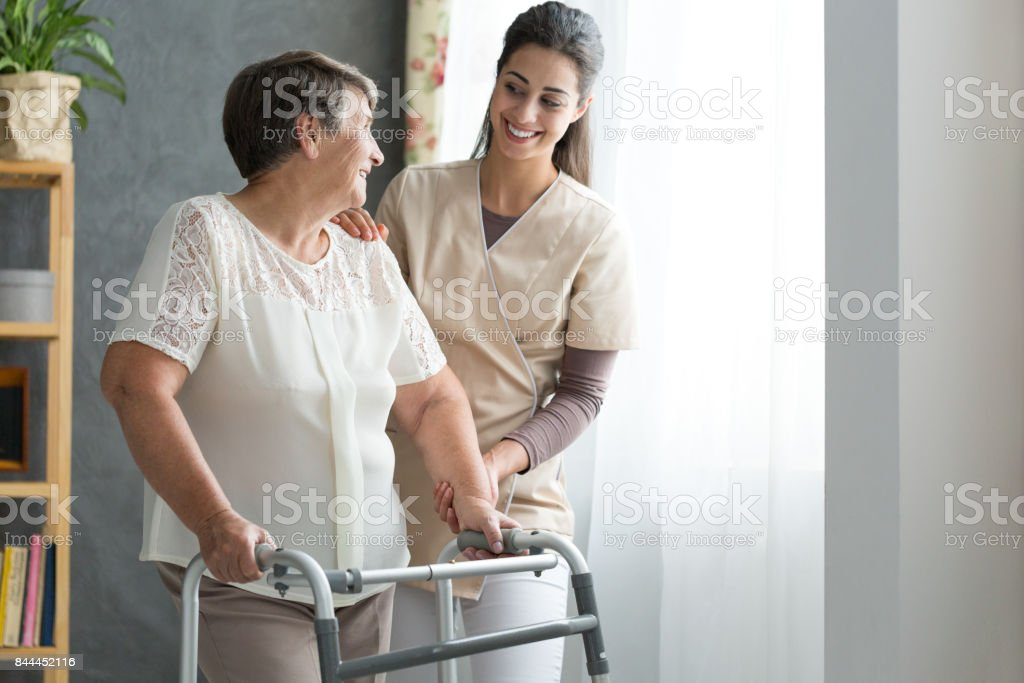 Nurse helping senior to walk stock photo