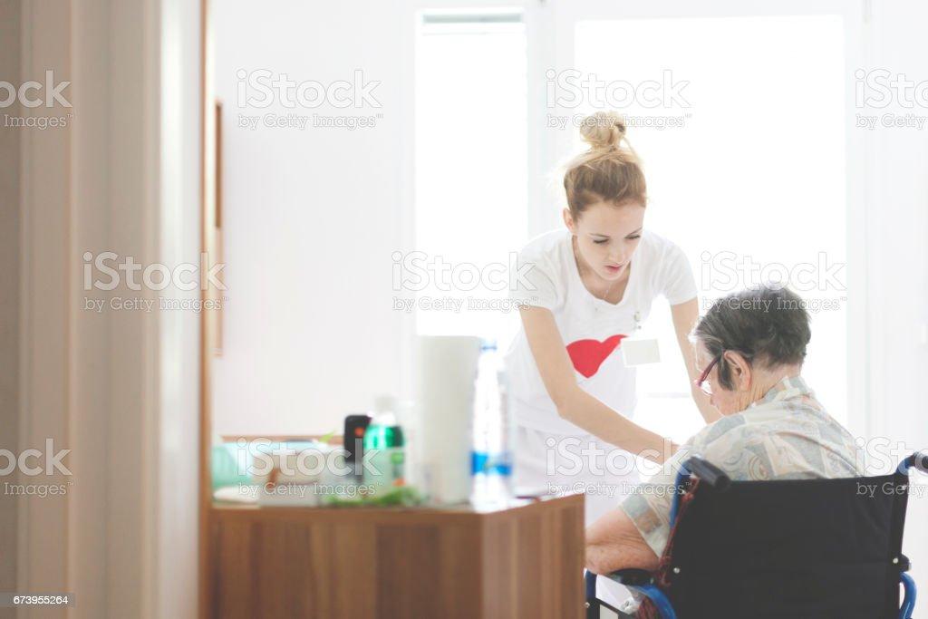 Nurse Helping Senior Woman Dressing stock photo