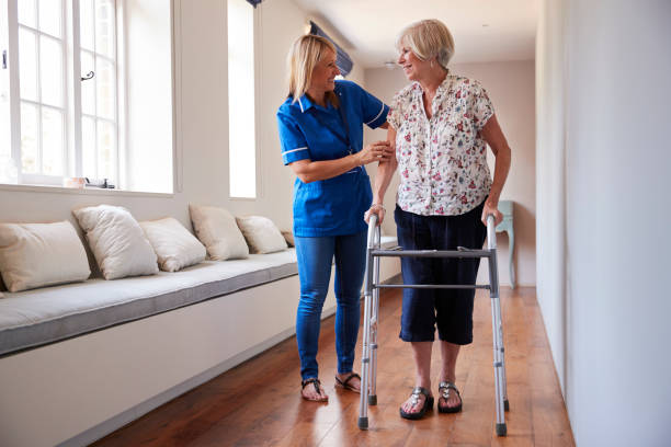 nurse helping senior woman use a walking frame - take care of your jeans imagens e fotografias de stock