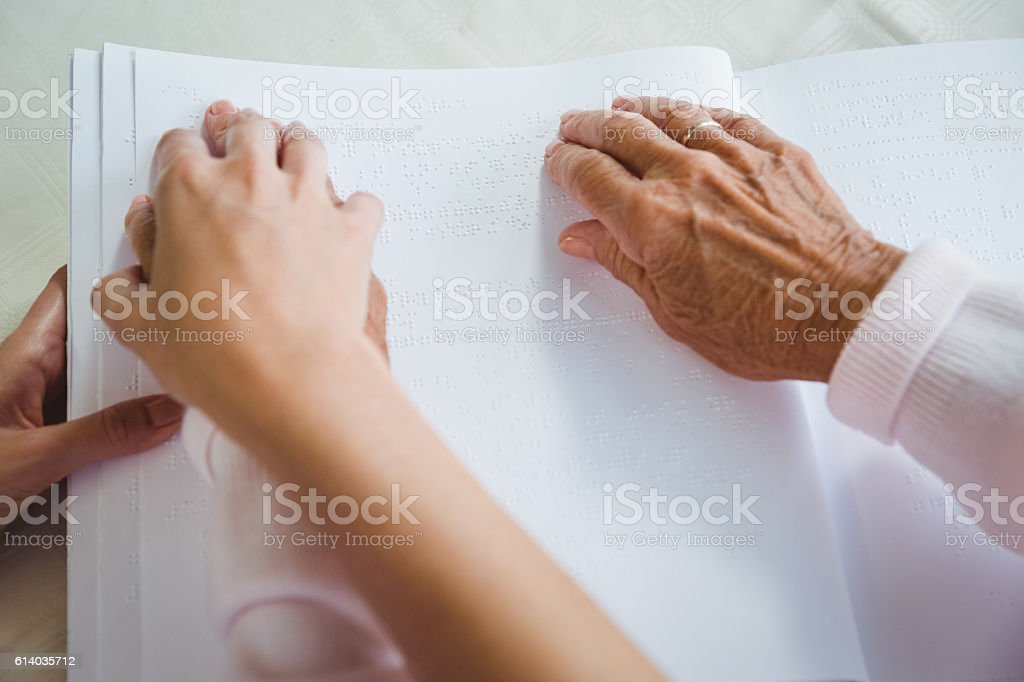 Nurse helping senior woman with braille stock photo