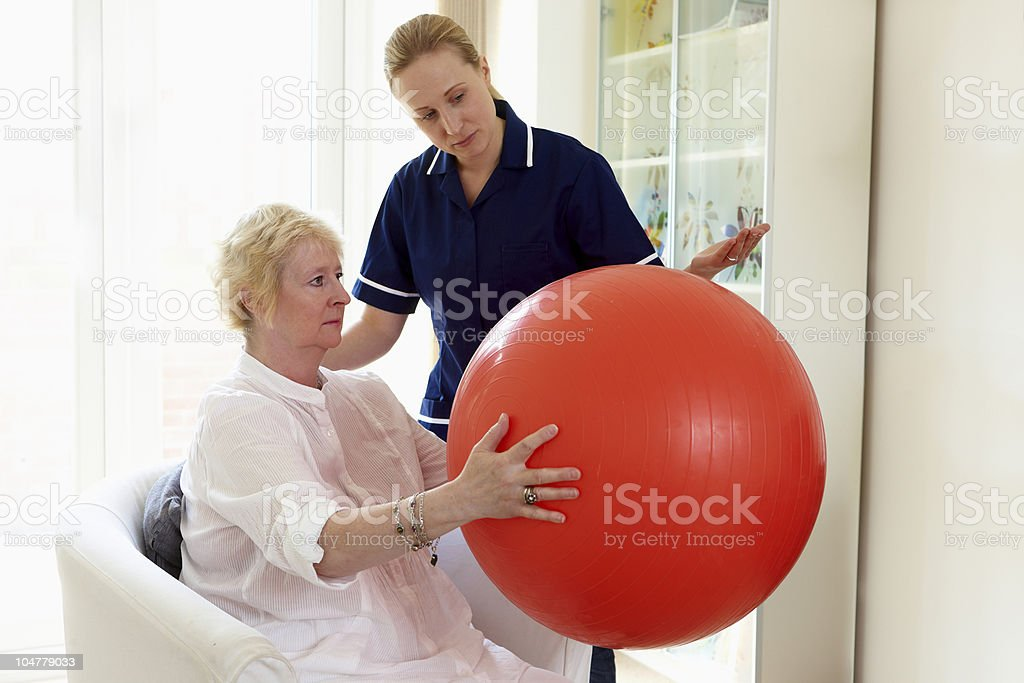 nurse helping senior woman with her rehabilitation exercises royalty-free stock photo