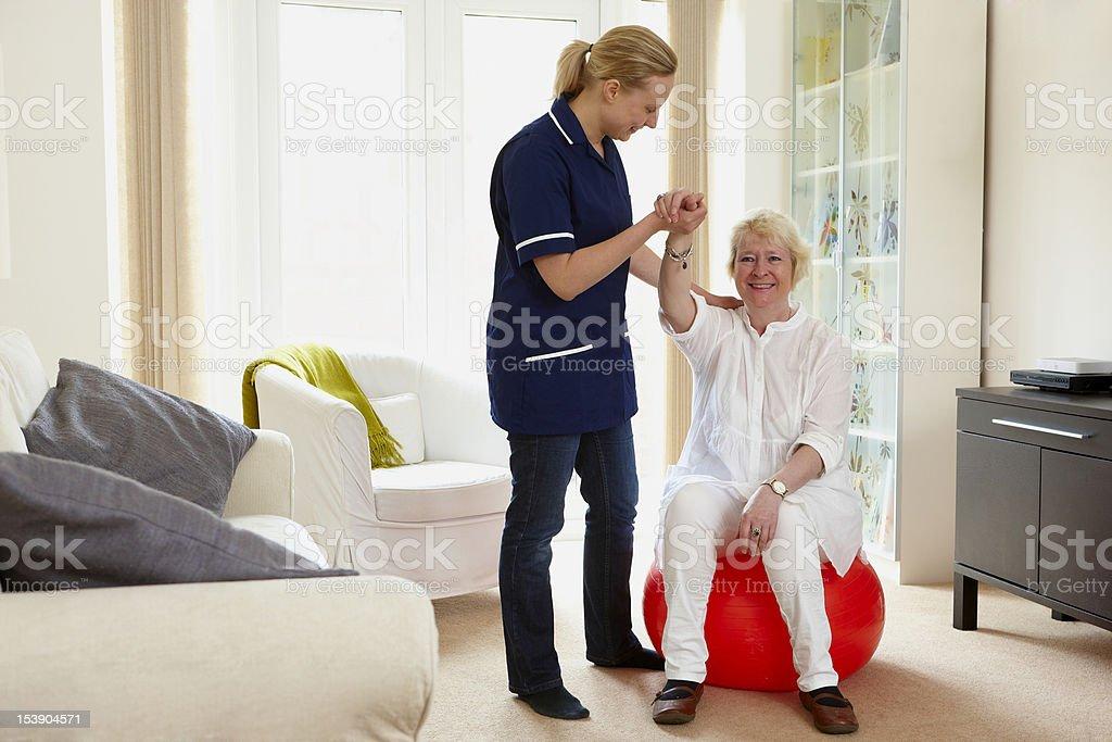 nurse helping senior woman with her rehabilitation exercises royalty-free stock photo