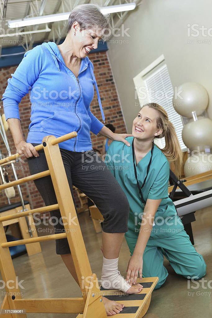 Nurse helping senior woman with physical therapy stock photo