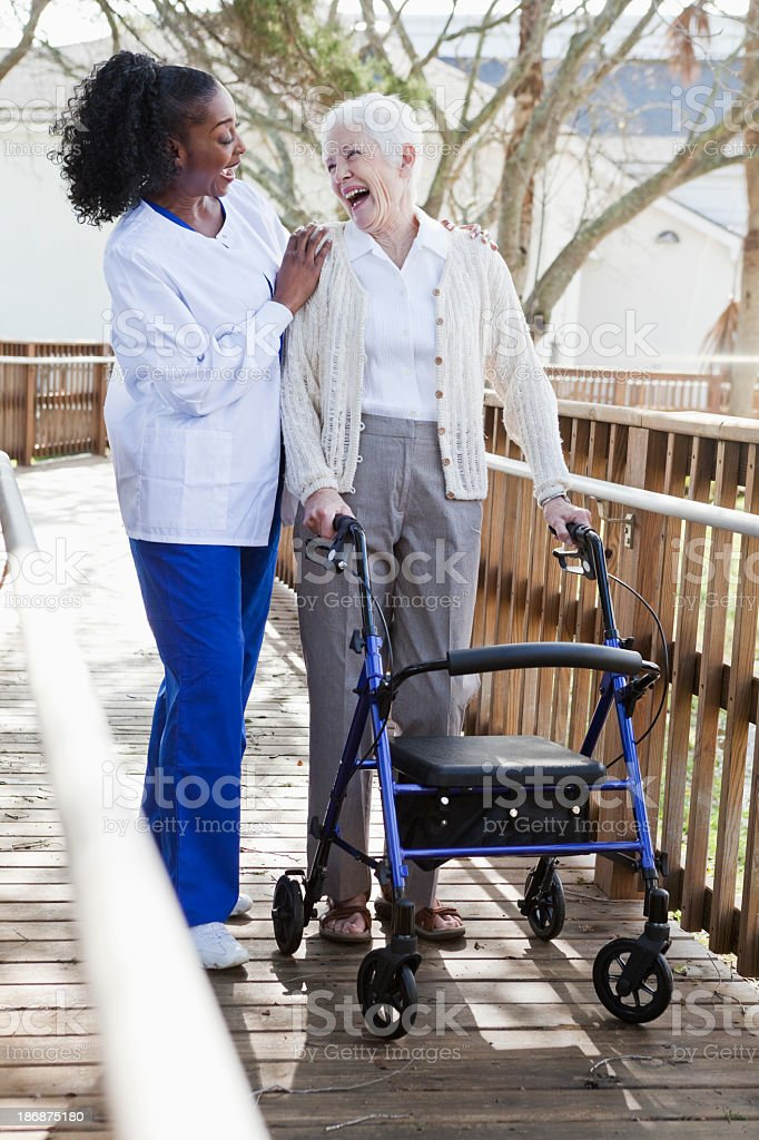 Nurse helping senior woman with walker royalty-free stock photo