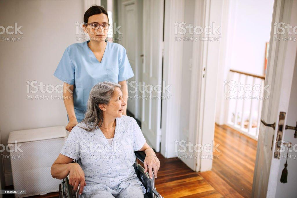 Nurse helping senior woman with wheelchair in nursing home