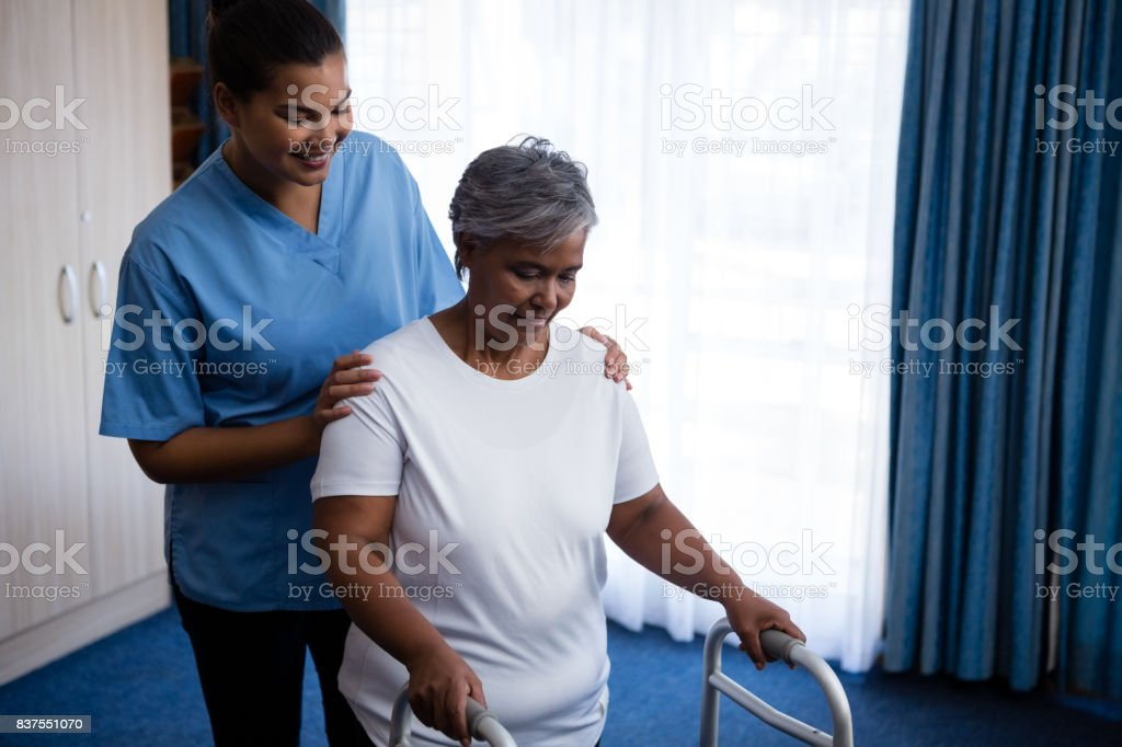 Nurse hepling senior woman in walking with walker stock photo