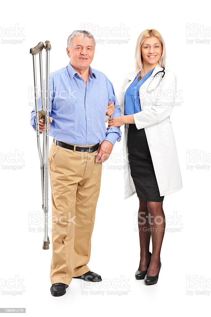 Nurse holding a senior patient with crutches royalty-free stock photo