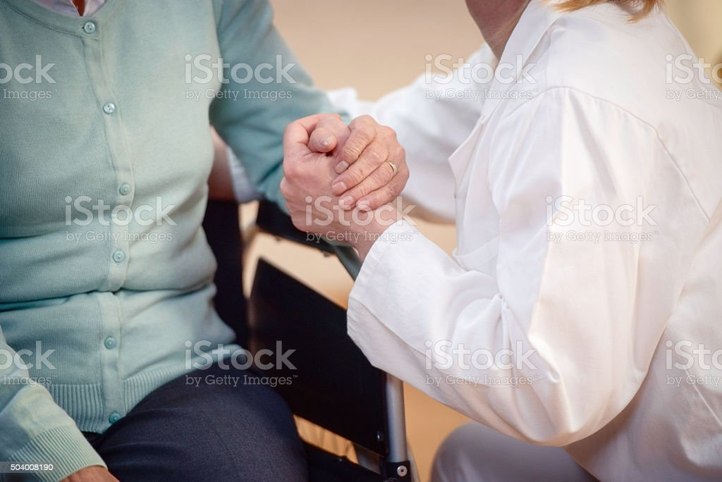 A nurse in a white coat tending to a disabled senior person, giving...