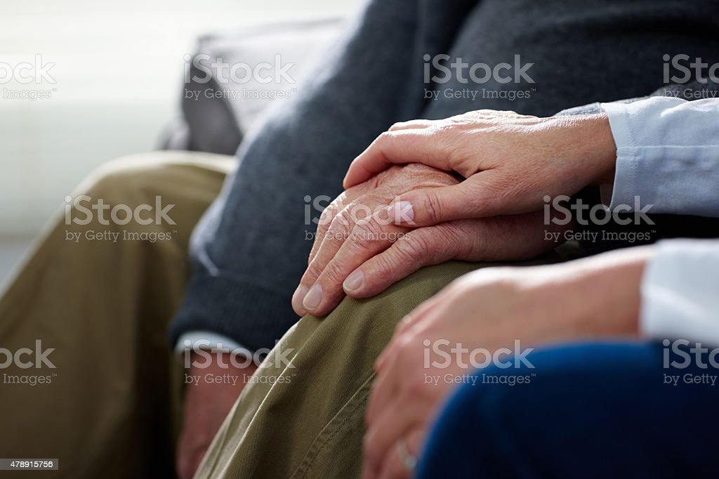 Nurse holding hand of senior male patient stock photo