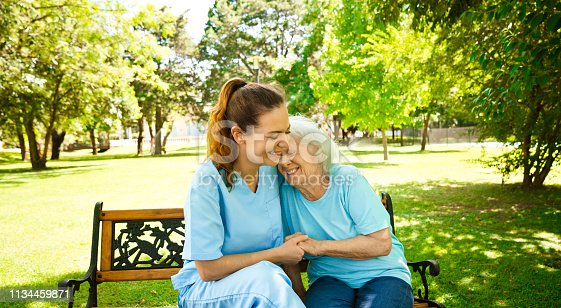 Smiling nurse holding hands of retired female sitting on bench. Senior woman is with healthcare worker. They are at back yard of nursing home.