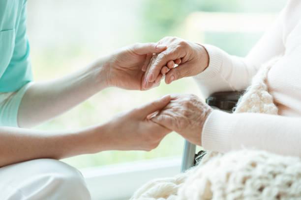 Nurse holding patient's hands stock photo