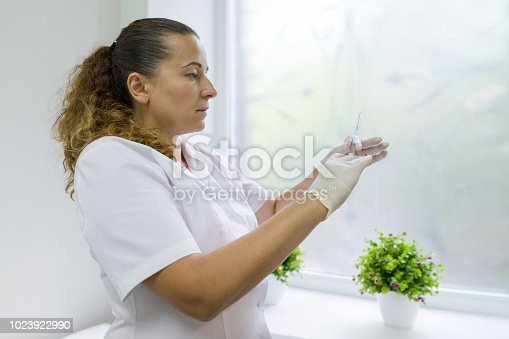 istock Nurse holds a syringe, prepares for an injection, in hospital against the window. 1023922990