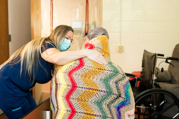 Nurse hugging a patient A blond nurse wearing dark navy scrubs and face mask uses her stethoscope to  listen to the lungs of a patient in a medical facility, Midwest, USA inpatient stock pictures, royalty-free photos & images