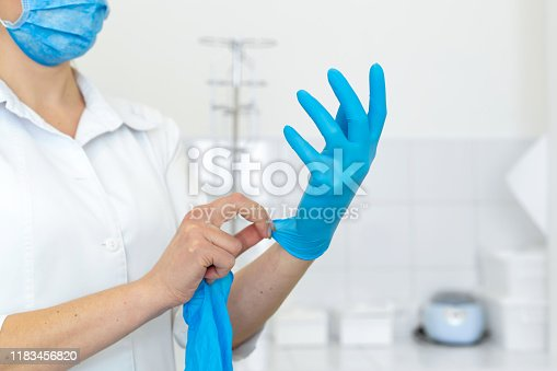 A nurse in a white coat puts on rubber gloves before a medical procedure in a bright handling room