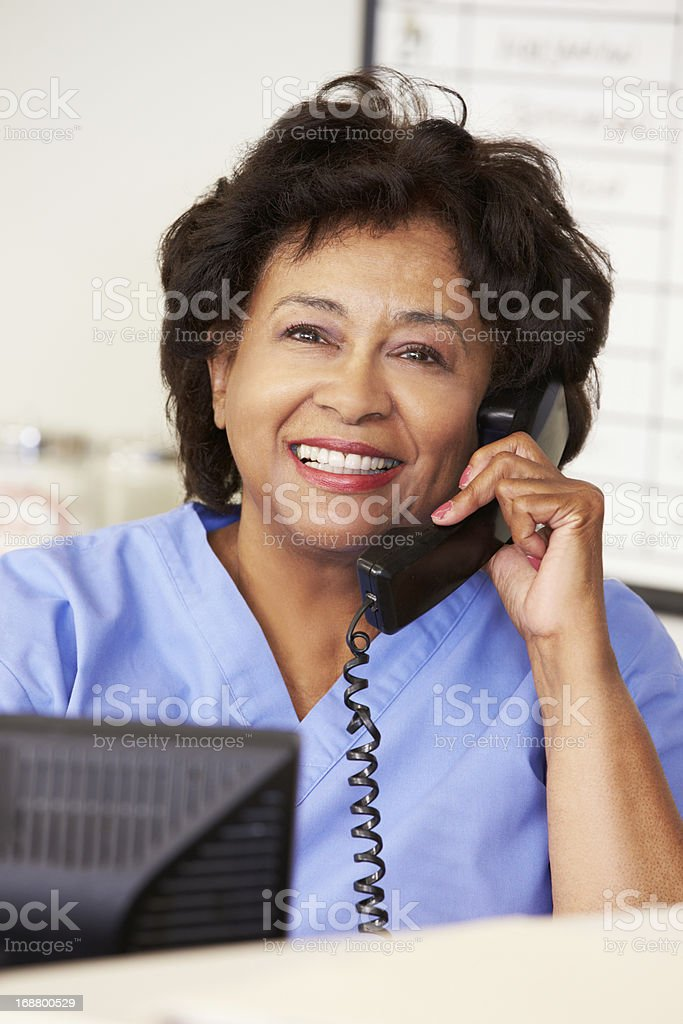 A nurse in blue making a phone call at the hospital  royalty-free stock photo