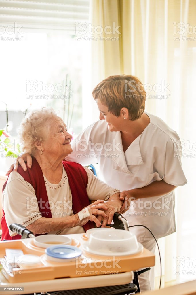 Nurse In The Nursing Home Bringing Lunch To A Senior Woman