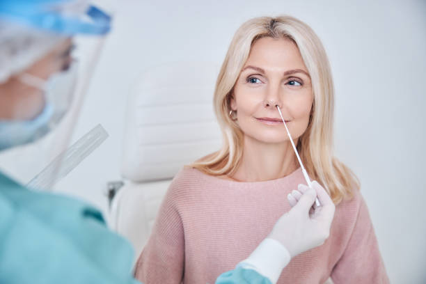 Nurse inserting the swab into the woman nostril stock photo