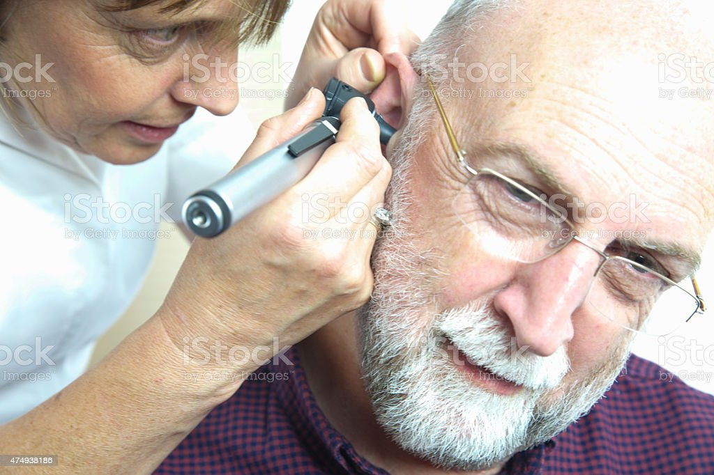 Nurse inspects patient's ear with an auroscope stock photo
