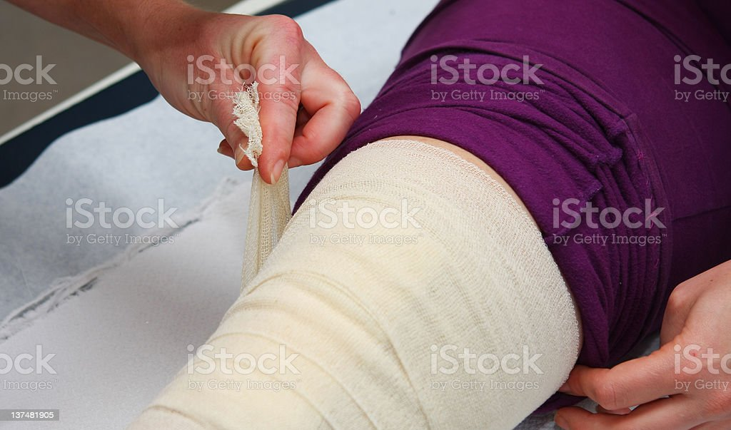 Nurse is changing bandage to a patient after knee operation... royalty-free stock photo