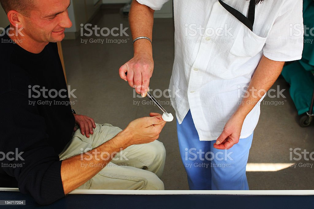 Nurse is changing bandage to a wounded patient's finger stock photo
