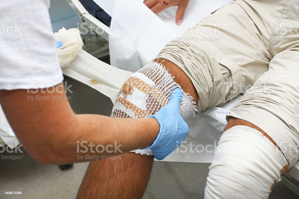Nurse is taking care of patient with the wounded knee royalty-free stock photo