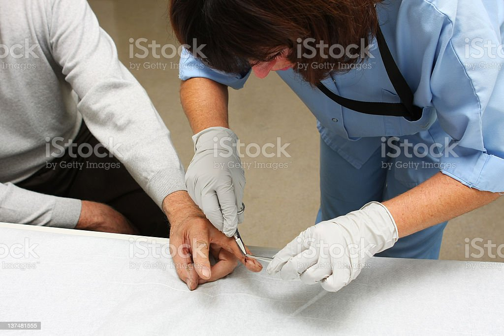 Nurse is taking care of the wounded patient...removing stitches stock photo