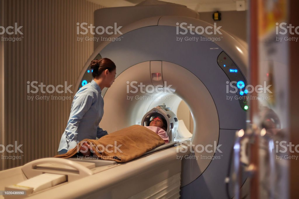 Nurse Looking At Girl During Cat Scan Exam stock photo